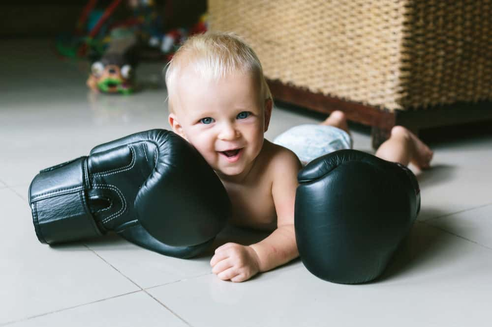 Happy smiling little baby boy with boxing gloves