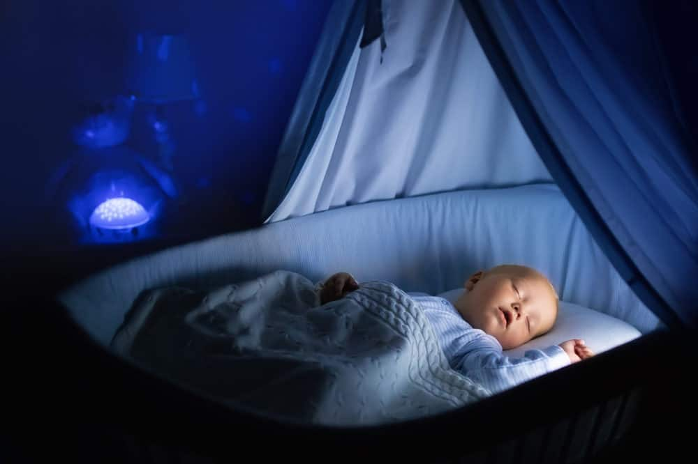 Cute baby soothed to sleep with a night projector