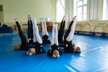 Young gymnasts doing exercises on gymnastics mats