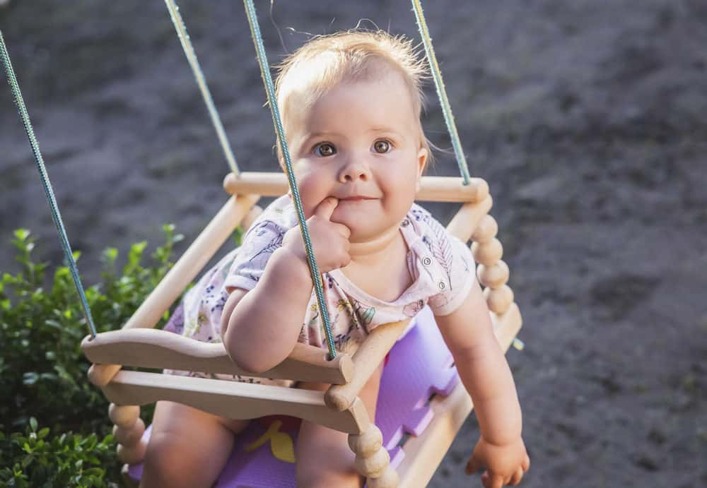 Adorable baby in an outdoor swing