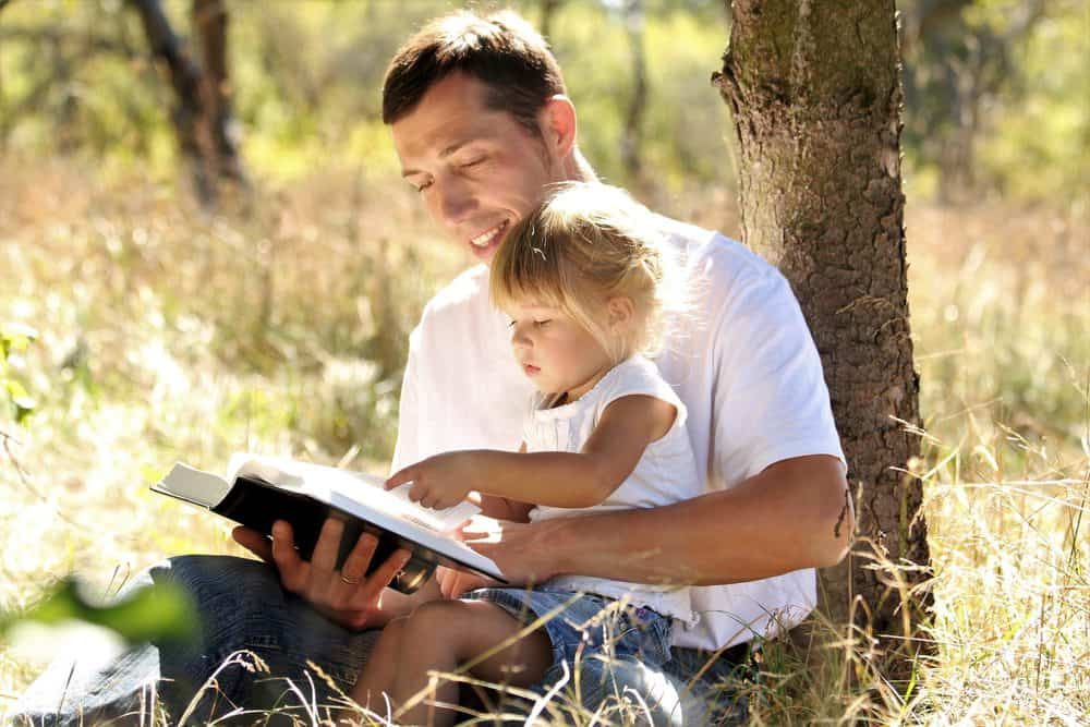 Sweet father reading the bible with his daughter