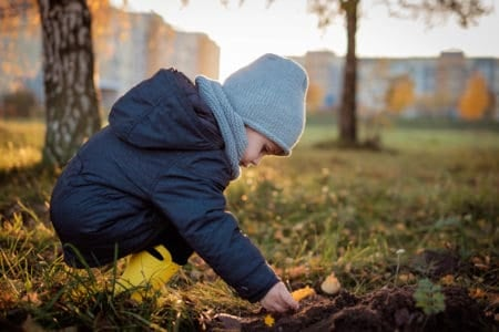 Beautiful toddler playing with earthy soil