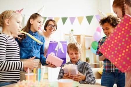 14 year old boy receiving gifts from his friends during birthday party