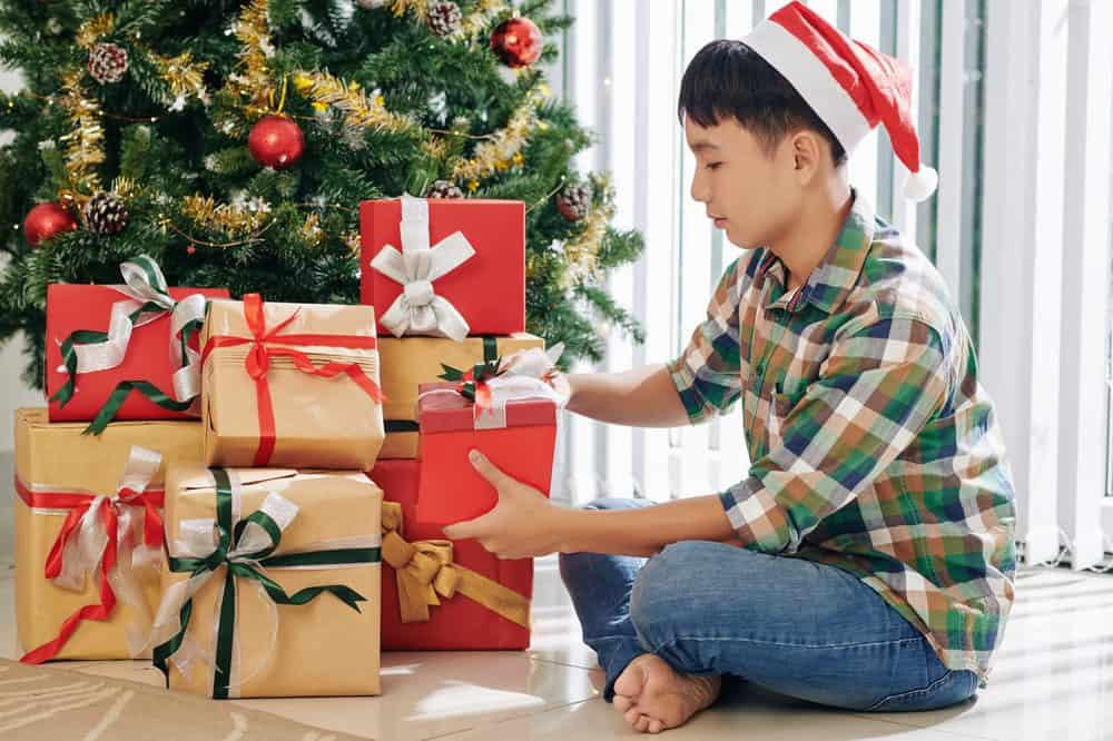 Teenage boy opening presents by the Christmas tree