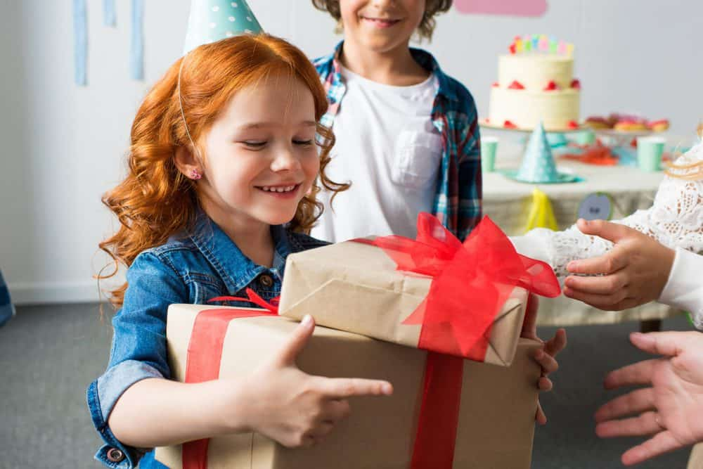 Nine year old little girl receiving a birthday gift