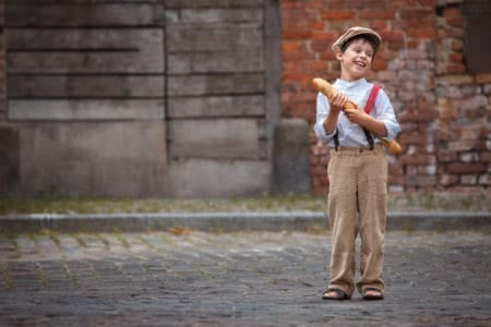Cheerful smiling french boy with baguette