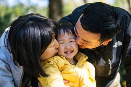 Happy japanese parents kissing their daughter on the cheeks