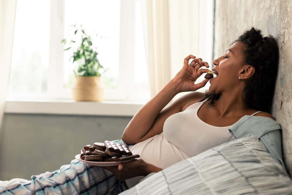 Beautiful pregnant woman eating chocolate on the bed