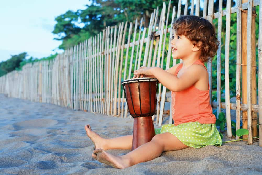 Little happy girl playing traditional african hand drum djembe