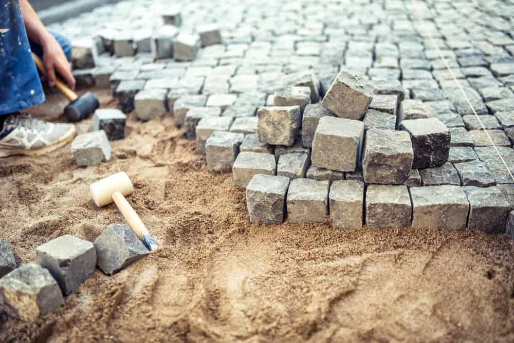 man laying stone bricks