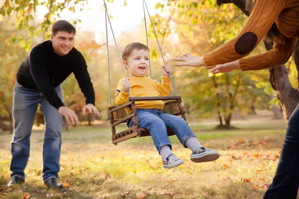 Mom and dad pushing toddler on an outdoor swing