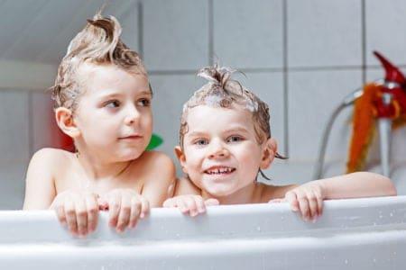 Two little boys shampooing their hair in the bathtub