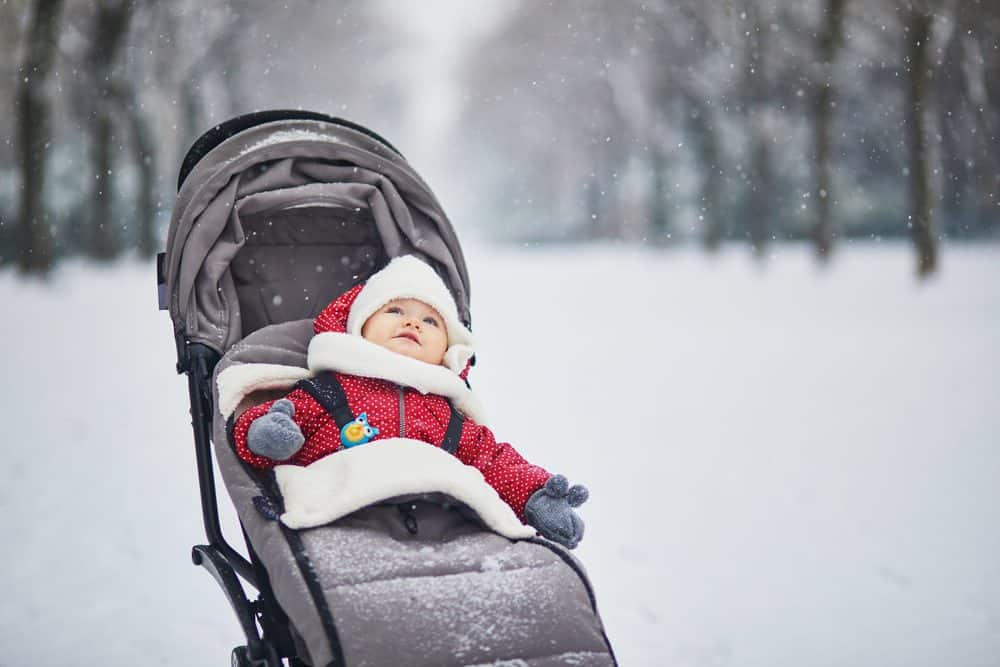 Baby girl out in the snow in stroller with footmuffs