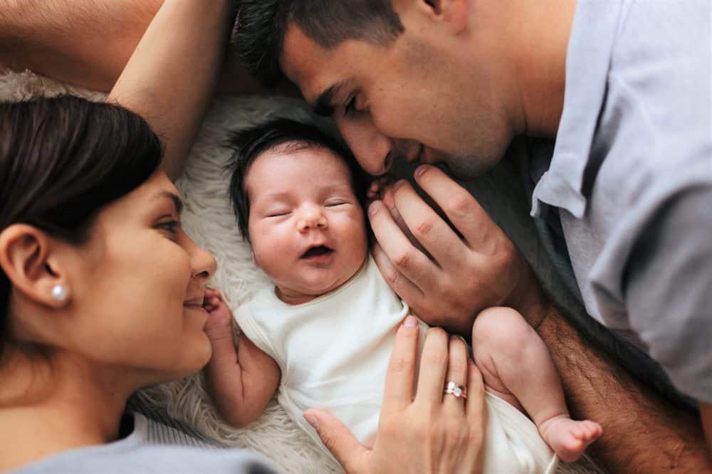 Portrait of happy parents cuddling their newborn baby