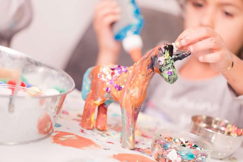 Little girl decorating unicorn paper mache