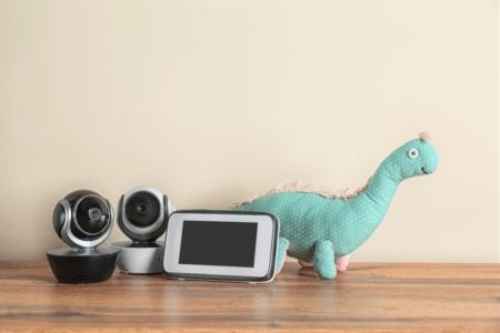 Dual screen baby monitors and toy on wooden table