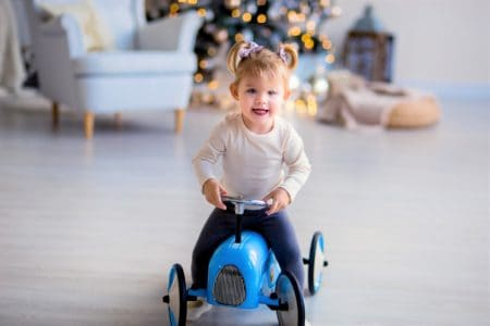Cute little girl sitting on a ride on toy with steering wheel