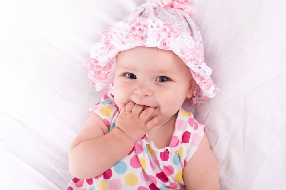Cute little girl with her hands in her mouth