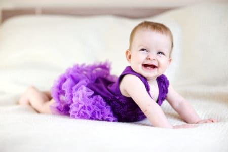 Beautiful baby girl smiling in her purple tutu