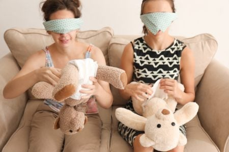 Two women putting diapers on toys at baby shower party