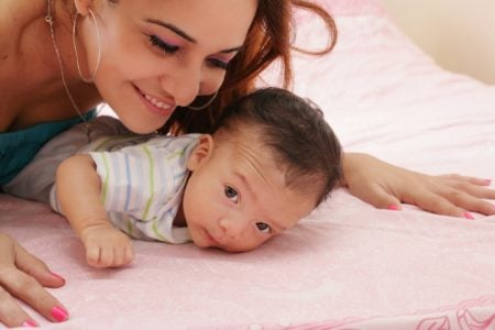 A hispanic mother leaning over her baby