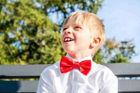 Happy boy dressed in white shirt with red bow tie